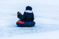 Baby winter sledding on the Ural River. Stock Photo