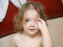Baby wipes his eyes after swimming handle Royalty Free Stock Photos