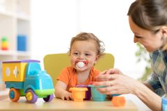 Baby and woman playing with puzzle toy in daycare or kindergarten Stock Images