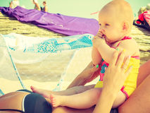 Baby on woman stomach on beach Stock Photography
