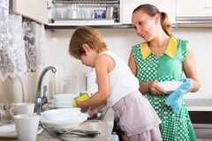 Baby with woman washing plates Royalty Free Stock Images