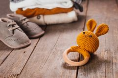 Baby wooden toy bunny near baby booties and clothes. On rustic wooden background. Selective focus stock photo