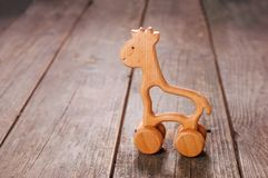 Baby wooden toy giraffe on the wheels on rustic wooden background. With blank space for text stock photography