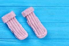 Baby wool socks on blue background. Pair of light pink baby-girl warm knitted socks on sale Stock Image