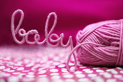 Baby word made of yarn among pink textile Stock Photos
