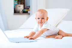 Baby working. Cute baby with computer (laptop) as if  working Royalty Free Stock Images