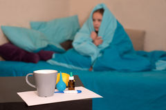 Baby wrapped in a blanket. On the table is a cup, a thermometer and a lemon and syringe Stock Photo