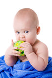 Baby wrapped in a blue towel biting green ball Royalty Free Stock Images
