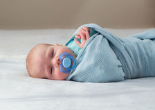 Baby wrapped sleeping. Baby wrapped in blue blanket sleeping stock photos