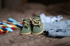 Baby's Green and Beige Sneakers on Brown Textile Royalty Free Stock Image