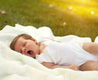 Baby yawing on the blanket on the grass Royalty Free Stock Images