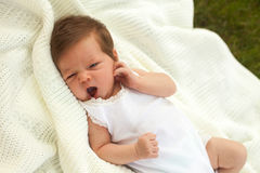 Baby yawing on the blanket on the grass Royalty Free Stock Photo