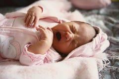 Baby yawn. Newborn baby girl wearing pink yawning and tired Royalty Free Stock Image