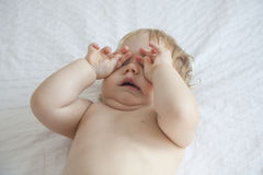 Baby yawning on white bed. One year blonde baby diaper yawning and touching her eyes over white bedcover stock images