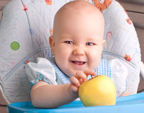 Baby with yellow apple Stock Photography