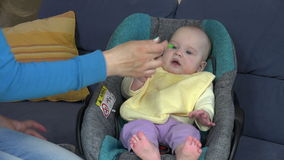 Baby with yellow bib eat vegetable pap sitting in car seat stock footage
