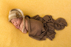Baby on yellow blanket. One week old newborn baby of mixed race sleeping on a soft yellow blanket stock photos