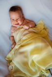 Baby in yellow blanket. On a white background Royalty Free Stock Photo