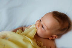 Baby in yellow blanket. On a white background Stock Photos