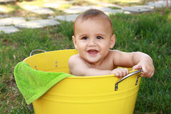 Baby in yellow bucket in garden. A six month old baby boy sits in a big yellow bucket and smiles.  He has two teeth on top and two on bottom.  He has a precious Royalty Free Stock Photo