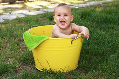 Baby in yellow bucket in garden Royalty Free Stock Photography
