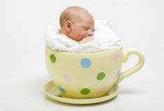 Baby in yellow spotted cup