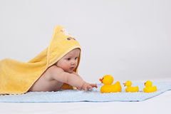 Baby in a yellow towel. Baby playing with 3 ducks in a yellow towel, trying to reach with one hand a duck Royalty Free Stock Photos