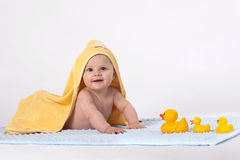 Baby in a yellow towel. Baby with a yellow towel after bath laughing Royalty Free Stock Photos