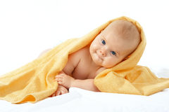 Baby in yellow towel. Adorable happy baby in yellow towel on white background stock photo