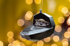 Baby Yoda in craft paper ornament against a a blurred background