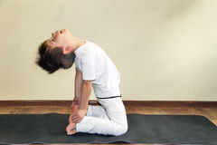 Baby yoga at home. The little boy does exercise Stock Image