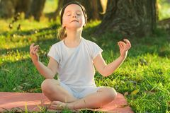 Baby yoga Lotus pose.. a child practicing yoga outdoors. Baby sitting in lotus pose with eyes closed stock photo