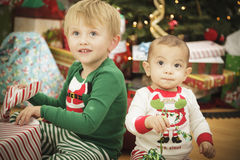 Baby and Young Boy Enjoying Christmas Morning Near The Tree Royalty Free Stock Photography