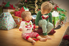 Baby and Young Boy Enjoying Christmas Morning Near The Tree royalty free stock photo