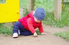 Baby zeigt etwas, das aus den Grund sitzt Lizenzfreie Stockbilder