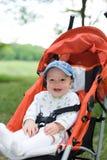 Baby in zittingswandelwagen op aard Stock Afbeelding