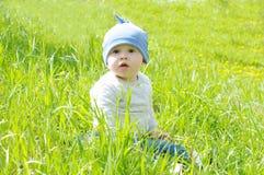 Babyalter von 8 Monaten, die auf Gras sitzen Stockfotografie