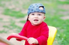 Babyalter von 10 Monaten schaukelt draußen im Sommer Stockfotos