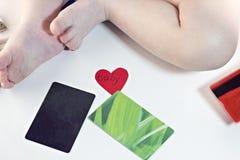 Babybeine und -Kreditkarten auf weißem Hintergrund, Herzbaby Stockfotografie