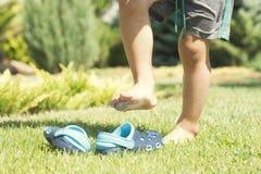 Babybenen en kinderen` s blauwe pantoffels op het groene gras in de tuin, schoenen voor kinderen, het concept gezond Royalty-vrije Stock Afbeeldingen