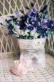 Babybeuten auf einem geflochtenen Stuhl und einem Blumenstrauß des Lavendels auf einem Ba stockfoto
