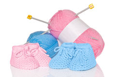 Babybeuten mit Wolle und Stricknadeln Stockbilder