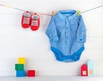 Babybeuten und blaues bodykit auf Wäscheklammern und hölzernen Spielwaren über weißem Hintergrund lizenzfreie stockfotos