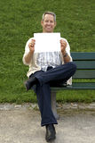 Babyboomer sitting and holding a blank sign Royalty Free Stock Image