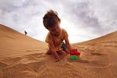 Babyboy dans un désert Images stock
