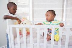 Babyboy jouant avec son frère dans son lit Photos libres de droits