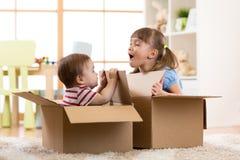 Babybruder und Kinderschwester, die in den Pappschachteln spielt lizenzfreies stockbild