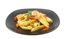 Babycorn y camarón sofritos en el plato aislado en blanco Imagenes de archivo