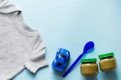 Babyebene legen mit Spielzeug, gesunder Nahrung und Stoff, blauer Hintergrund mit Kopienraum lizenzfreies stockfoto