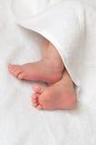 Babyfüße in einem weißen Tuch Stockbilder